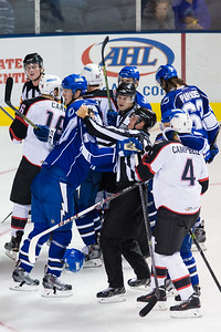 Mike Angelidis #10(C) of the Syracuse Crunch is restrained by Linesman Alex Stagnone (#7) and players come together late during the Portland Pirates regular season contest vs. the Syracuse Crunch at the Cross Insurance Arena in Portland, Maine on 10/25/2014. (Photo by Michael McSweeney/Portland Pirates)