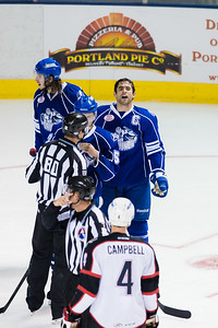 Mike Angelidis #10(C) of the Syracuse Crunch asks Andrew Campbell #4(D) of the Portland Pirates what kind of Pizza he likes during the Portland Pirates regular season contest vs. the Syracuse Crunch at the Cross Insurance Arena in Portland, Maine on 10/25/2014. (Photo by Michael McSweeney/Portland Pirates)