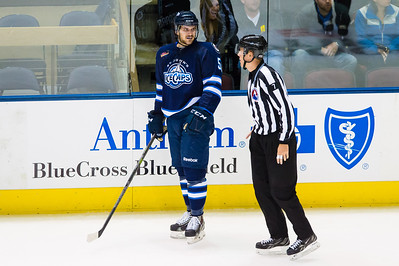 Austen Brassard #50(RW) of the St. John's IceCaps gets escorted to the penalty box by Linesman Alex Stagnone #7 during the Portland Pirates regular season contest vs. the St. John's IceCaps at the Cross Insurance Arena in Portland, Maine on 10/31/2014. (Photo by Michael McSweeney/Portland Pirates)