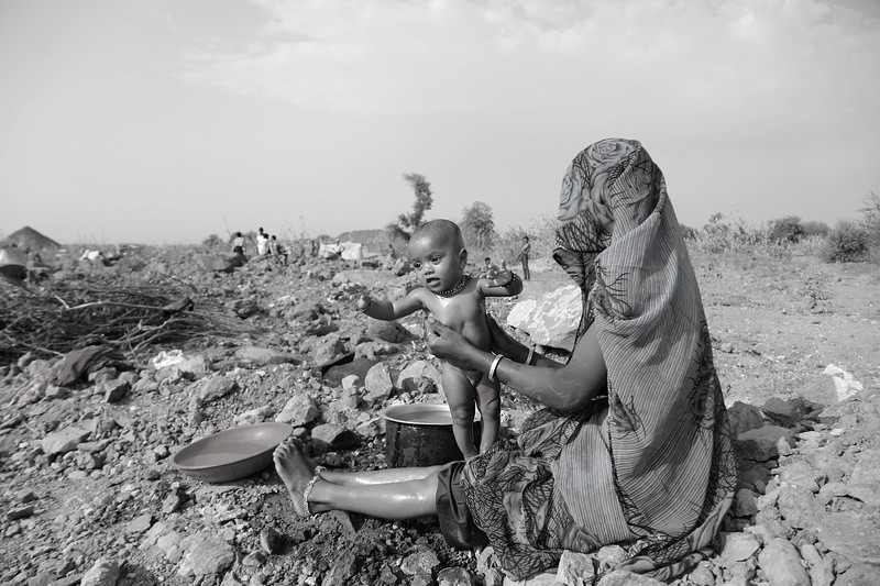 Woman in her early 20s washing her daughter at the construction site, a luxury she can't afford back home.