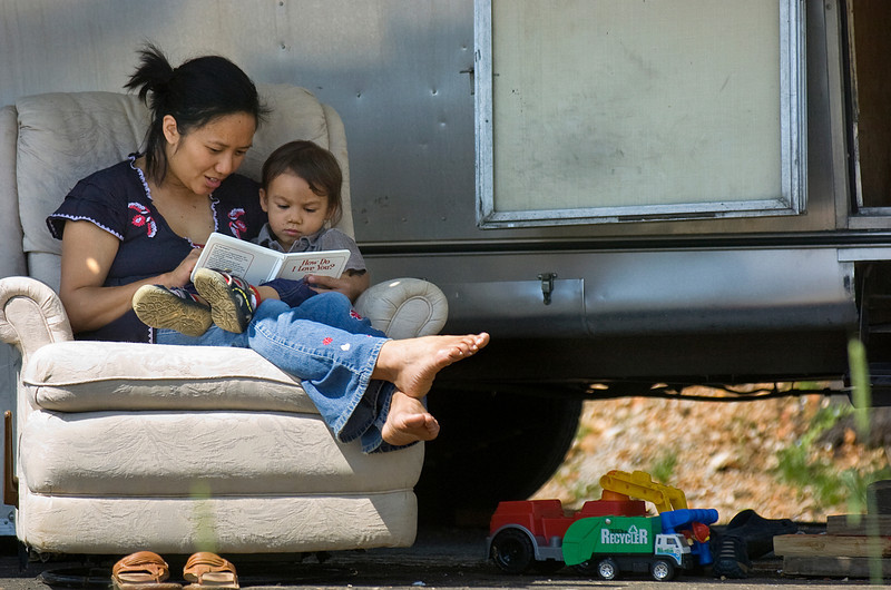 Orlene Gentile reads to her son, Gianluca, outside their trailer in Decatur, Ala. Sunday, April 26, 2009.