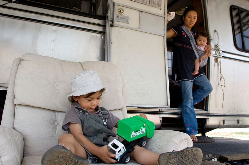 Orlene Gentile, right, (carrying her daughter, Giulia) keeps an eye on Gianluca as he plays outside their camper in decatur, Ala. Sunday, April 26, 2009.