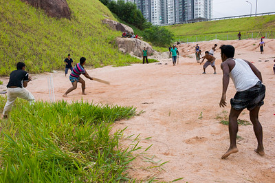 Bangladeshi workers are playing cricket at small open space near by their container houses.