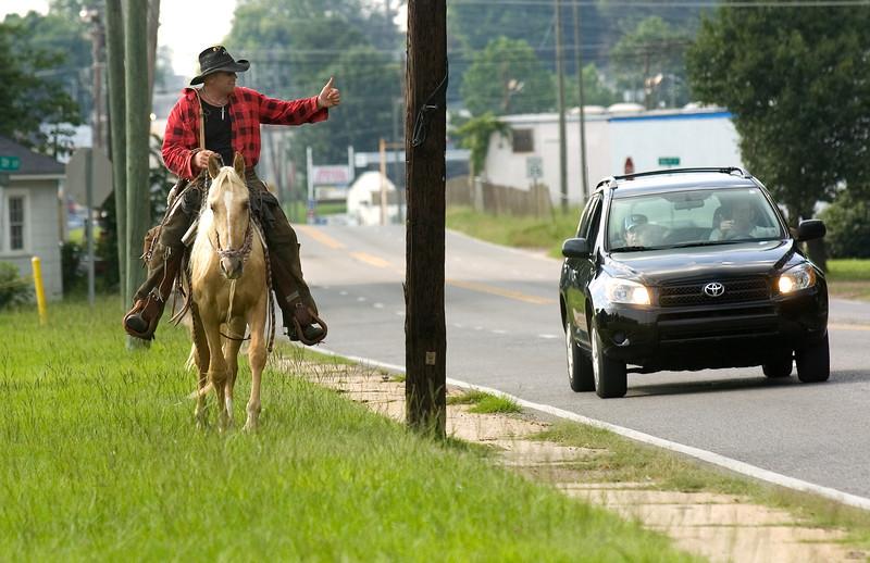 Drivers along AL-82 honk to greet Joe Guy, left, and he greets back Saturday, June 6, 2009.