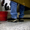 "Collis Crayton cleans a toilet at Decatur High School Thursday, January 15, 2009. ""I don't feel being a low-class person because of doing this Job,"" he says. ""I like helping people; that's why I don't mind cleaning, 'cause I feel I'm helping somebody along with helping myself."""