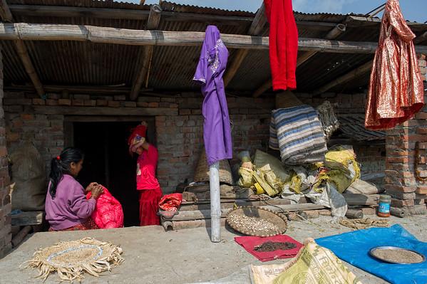 Kumari Diya is changing her clothes.  Kumaris's mother Tula Laxmi Bajracharya(50) is sewing Kumari's jacket at the rooftop. Bungamati, Nepal, 2014