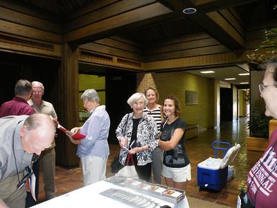 Bill Briggs '44 signs in. Dorothy Elliott '48, daughter Linda Elliott and granddaughter Lauren Elliott look on.