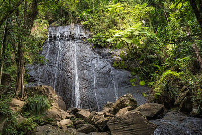 Waterfall cascading over a huge rock face in rainforest