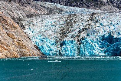 View of glacier face with blue snow and tourist boat