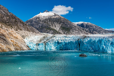 Wide angle view of glacier face with tourist boat and mountains