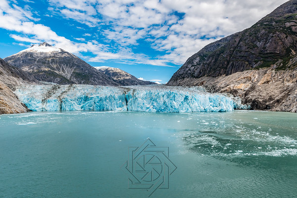 Long distance view of an Alaskan glacier with aqua icy waters