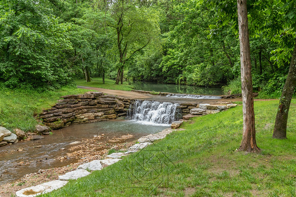 Stream through canyon park with cascading water over stone walkway