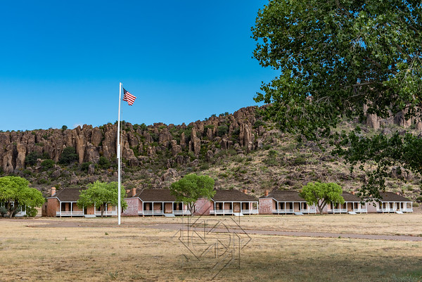 Fort Davis flag pole with old wooden structures in the background