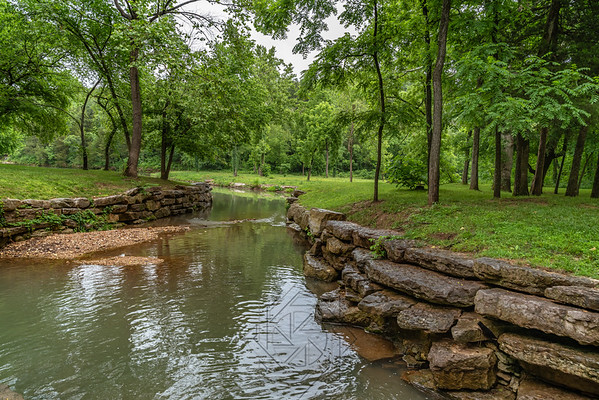 Stream through canyon park with stone walls