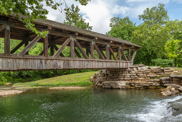 Wooden covered bridge over stream in canyon park