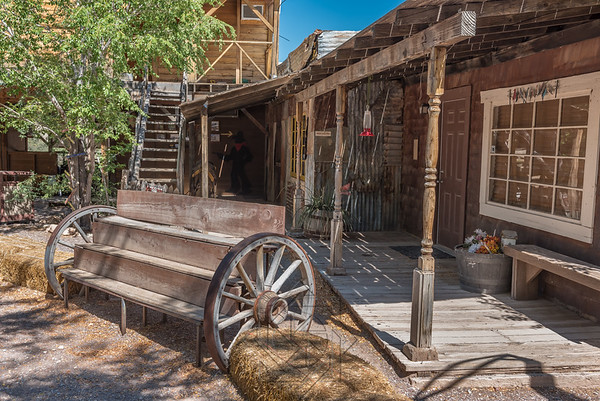 Western bench with wagon wheels next to western building
