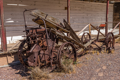 Old rusty iron vehicle frame with wooden seat