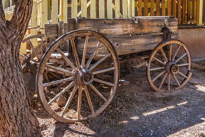Old wooden chuck wagon next to a tree trunck