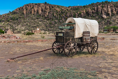 Side view of canvas covered wagon with green buck board