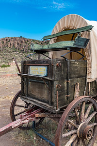 Front end of a covered wagon with green buck board