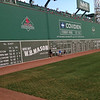 """Fans who just had their picture taken in front of the """"Green Monster""""<br /> Because of the ballpark's age and constrained location in the dense Fenway–Kenmore neighborhood, the park has had many renovations and additions over the years not initially envisioned, resulting in unique, quirky features, including """"The Triangle"""", """"Pesky's Pole"""", and most notably the famous Green Monster in left field."""