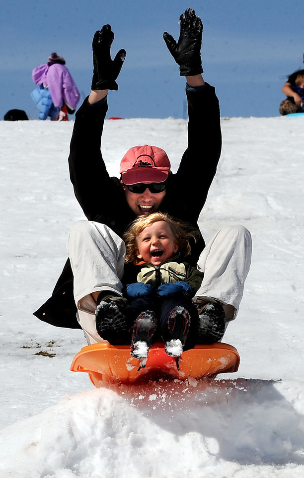 Sledding at Scott Carpenter59.JPG Garvin Heath and his son Aden, 2, go over a bump at Scott Carpenter Park on Sunday. There was still enough snow for sledding, but it is melting fast.<br /> Cliff Grassmick / March 21, 2010