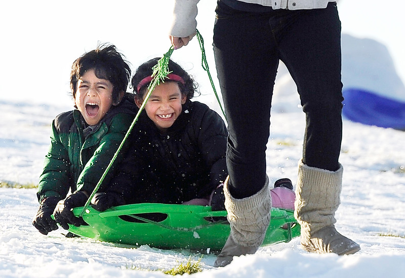 Sledding at Scott Carpenter.JPG Dany Monzon, 6, left, and his sister Sara Monzon, 7, scream with joy while being pulled down a hill by Hannah Levtert, 18, while sledding on Friday, Oct. 28, at Scott Carpenter Park in Boulder.<br /> Jeremy Papasso/ Camera