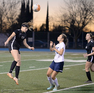 Chico's Isabel Bishop gets her head on a ball over PV's #24 (not on roster) during Chico High vs Pleasant Valley Girls soccer action at Pleasant Valley High School Wed. Feb. 7, 2018. (Bill Husa -- Enterprise-Record)