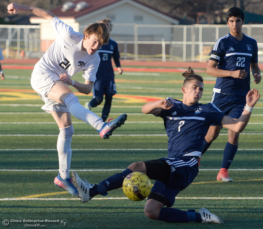 . Chico #21 Omar Camarena takes a shot as PV\'s Akia Ramirez adds pressure during Pleasant Valley vs Chico High Boys soccer action at Chico High Wed. Feb. 7, 2018. (Bill Husa -- Enterprise-Record)