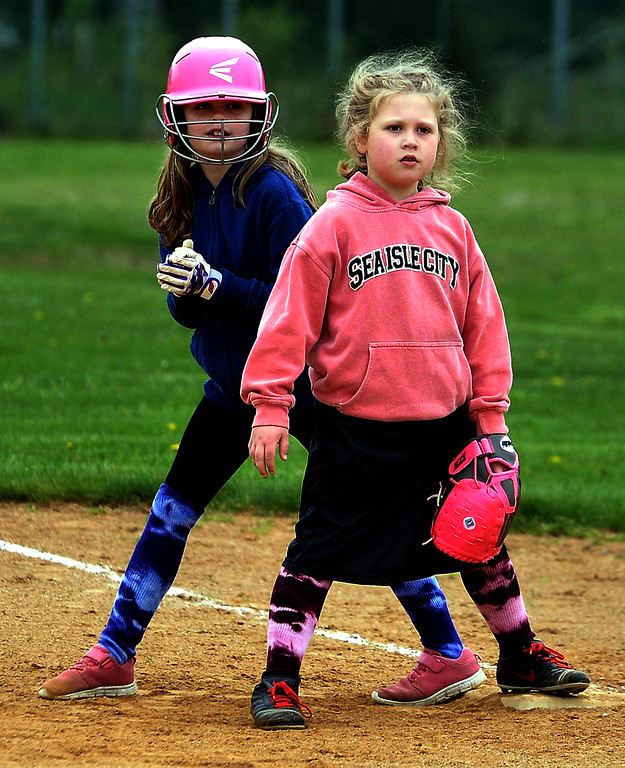 . First baseman Brinley Cafferky keeps an eye on the batter as Maddie Leibley gets ready to run at the North Penn Little League Softball opening day April 22, 2017.  (Bob Raines/Digital First Media)