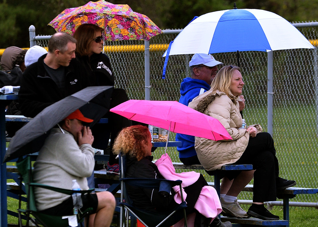 . Parents huddle under umbrellas against the drizzle at the North Penn Little League Softball opening day April 22, 2017.  (Bob Raines/Digital First Media)