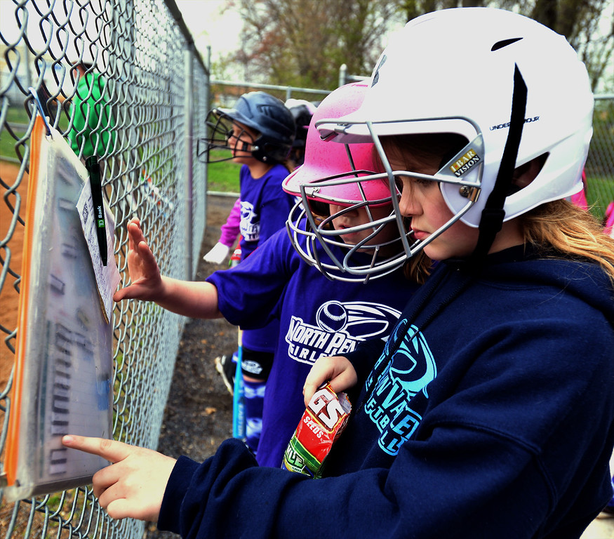 . Danielle Brasch and Ellie Huber check the batting order at the North Penn Little League Softball opening day April 22, 2017.  (Bob Raines/Digital First Media)