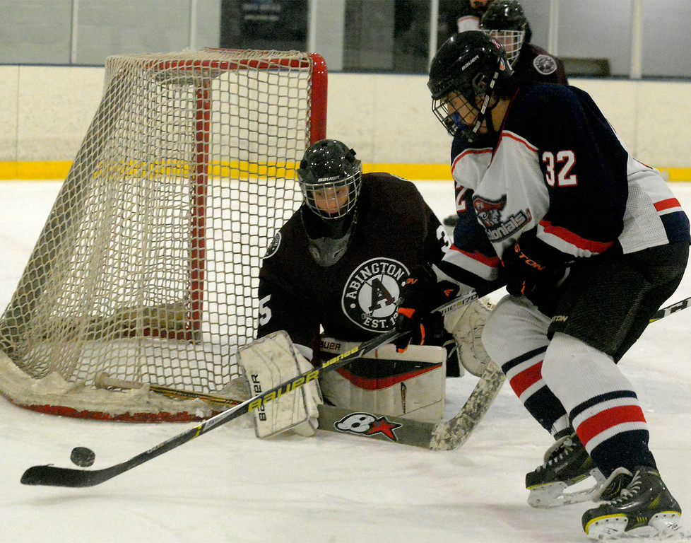 . Plymouth Whitemarsh\'s Desmond Brock takes the puck behind the cage as Abington goal keeper Jacob Snellenburg blocks him from feeding a backhand pass out to the front Dec. 6, 2017. (Bob Raines--Digital First Media)