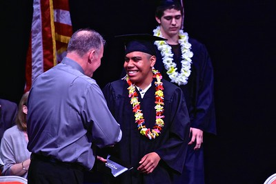 Steven Ramirez is all smiles as he receives his Pacific Coast High School diploma from Pacific Coast High principal Jon Larson on Tuesday night.  (Jose Quezada — For Times-Standard)
