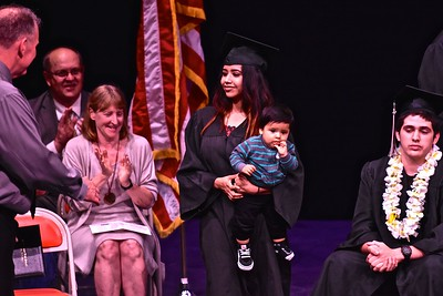 Ericka M. Hernandez holds her toddler while receiving her Pacific Coast High School diploma from Pacific Union High principal Jon Larson on Tuesday night. (José Quezada—For the Times-Standard)