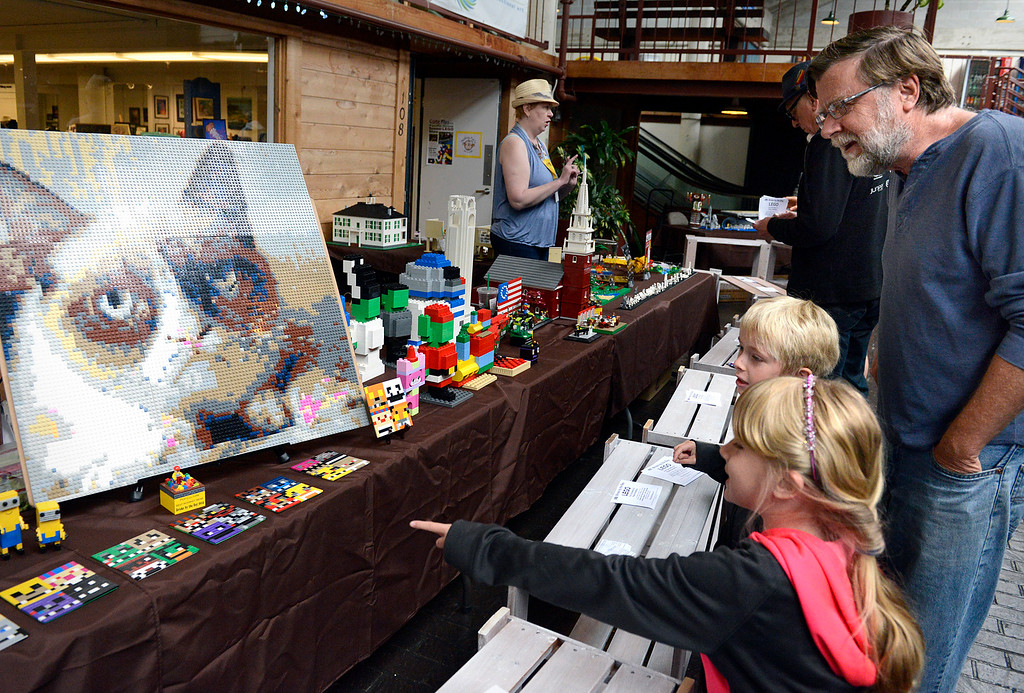 . Twins Carson and Gracie Miller, 7, look at a picture of a cat with their father Dan during the Pacific Grove Summer LEGO show inside the American Tin Cannery on Saturday July 2, 2016.  (David Royal - Monterey Herald)