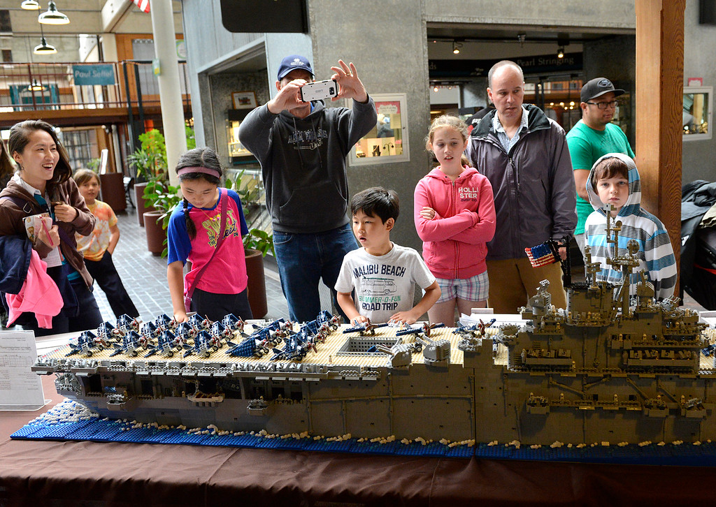 . Visitors to the Pacific Grove Summer LEGO Show are awed by Marcello De Cicco\'s LEGO model of the USS Yorktown CV10 World War II era aircraft carrier inside the American Tin Cannery on Saturday July 2, 2016. The 8 1/2 foot boat is made up of over 26,000 LEGO bricks and weighs 76 pounds. The event was sponsored by the Bay Area LEGO users group which draws members from as far away as north of San Francisco, east of Oakland and down into Monterey County. (David Royal - Monterey Herald)