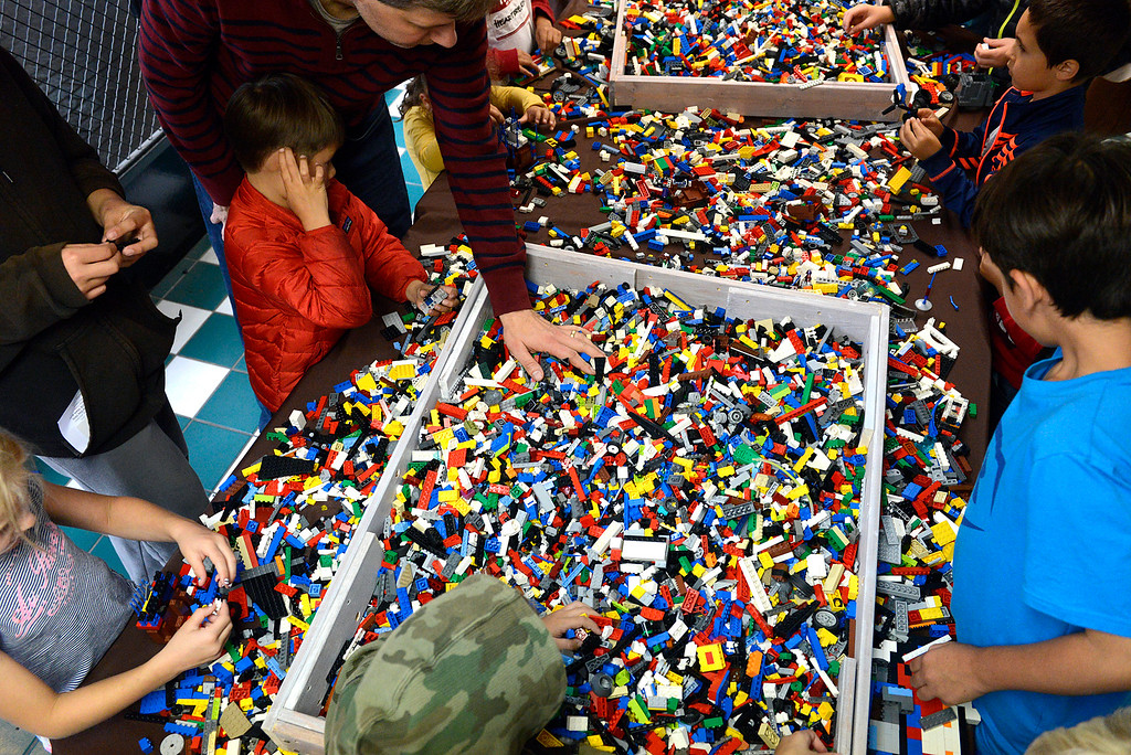 . Children and an occasional parent put together blocks in a LEGO build area during the Pacific Grove Summer LEGO show inside the American Tin Cannery on Saturday July 2, 2016.  (David Royal - Monterey Herald)