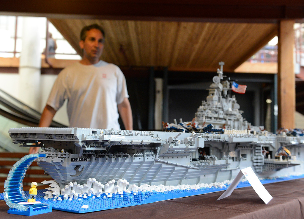 . LEGO waves over a surfer and off the stern of Marcello De Cicco\'s (at rear of photo) LEGO model of the USS Yorktown CV10 World War II era aircraft carrier during the Pacific Grove Summer LEGO Show inside the American Tin Cannery on Saturday July 2, 2016. The 8 1/2 foot boat is made up of over 26,000 LEGO bricks and weighs 76 pounds. The event was sponsored by the Bay Area LEGO users group which draws members from as far away as north of San Francisco, east of Oakland and down into Monterey County. (David Royal - Monterey Herald)