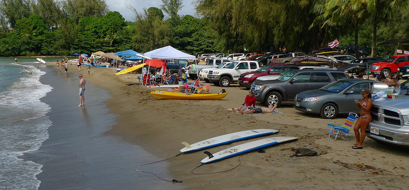 Car's parked up on the beach at Hanalei Bay.