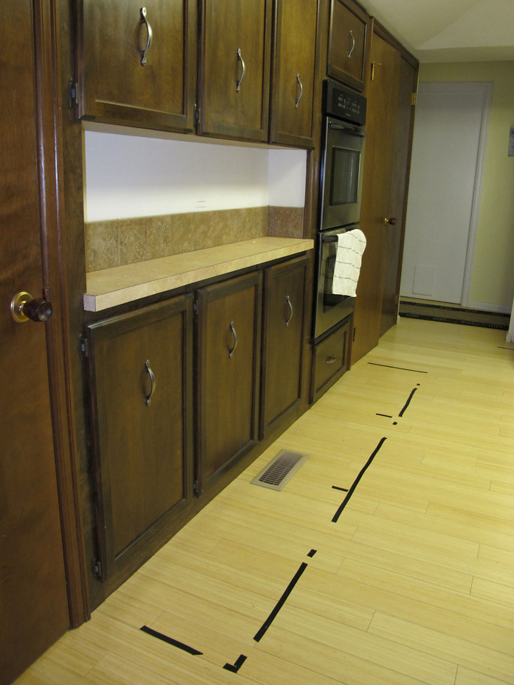 Old kitchen with tape on floor to show where new cabinets & fridge will go.