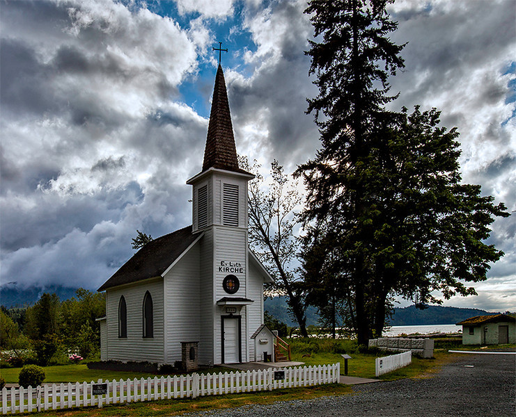 "The Little White Church of Elbe, Evangelical Lutheran, Elbe, Washington. On the steeple is ""Ev. Luth. KIRCHE"" (Evangelische Lutherische Kirche), a reminder of the founders' German origins. The 18 x 24 foot church was built in 1906. Forged by the town's first blacksmith, a 4-foot iron cross tops the 46-foot steeple, which houses the bell."