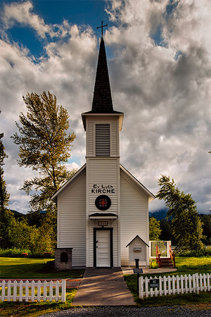 "The Little White Church of Elbe, Evangelical Lutheran, Elbe, Washington. The Little White Church of Elbe, Evangelical Lutheran, Elbe, Washington. On the steeple is ""Ev. Luth. KIRCHE"" (Evangelische Lutherische Kirche), a reminder of the founders' German origins. The 18 x 24 foot church was built in 1906. Forged by the town's first blacksmith, a 4-foot iron cross tops the 46-foot steeple, which houses the bell."