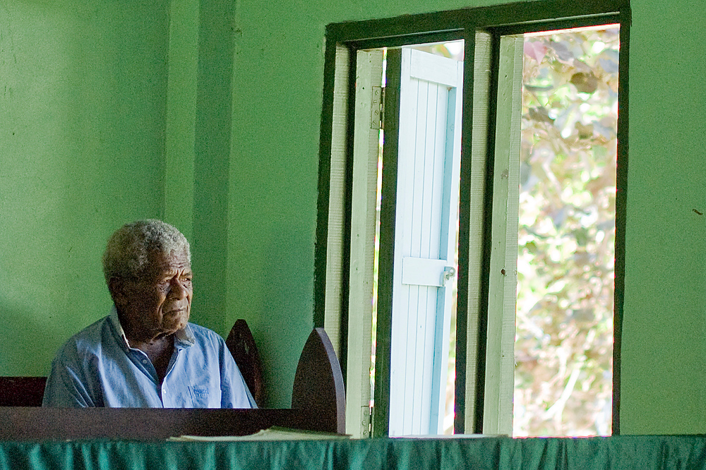 Village Elder Looking Out A Window at a Fijian Church Service