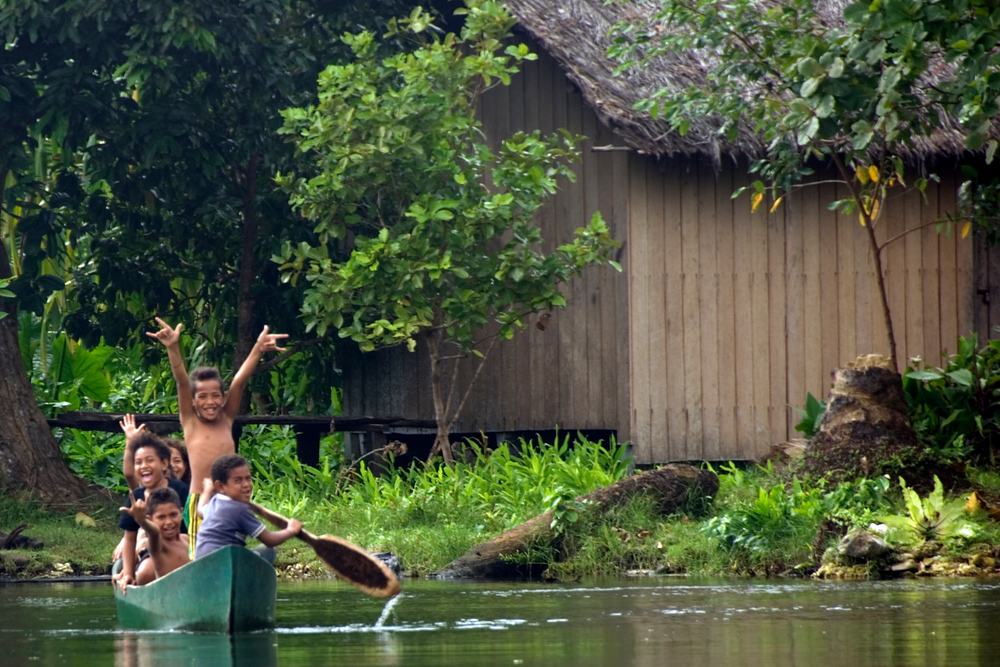 Children in a canoe, Rennell Island, Solomon Islands