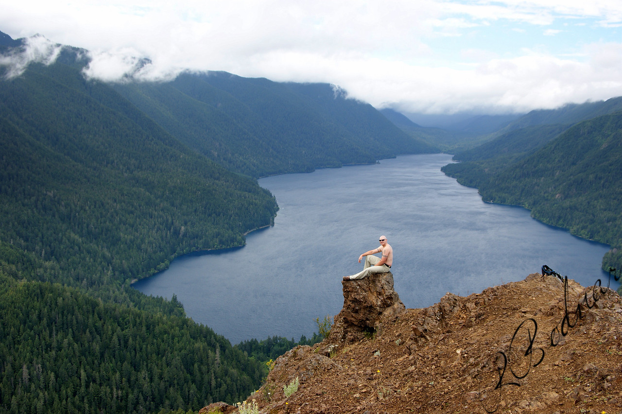 Photo By Bob Bodnar..........................Greg on the summit of Storm King Mountain, with a view of Lake Crescent                                                       <br />  Lake Crescent is a deep lake located entirely within Olympic National Park in Clallam County, Washington, United States, approximately 17 miles  west of Port Angeles, Washington on U.S. Route 101 and nearby to the small community of Piedmont. At an official maximum depth of 624 feet (190 m), it is officially the second deepest lake in Washington, although unofficial depth measurements of more than 1,000 feet  have been recorded. <br />  <br /> Lake Crescent is known for its brilliant blue waters and exceptional clarity, caused by a lack of nitrogen in the water which inhibits the growth of algae. It is located in a popular recreational area which is home to a number of trails, including the Spruce Railroad Trail, Pyramid Mountain trail, and the Barnes Creek trail to Marymere Falls.