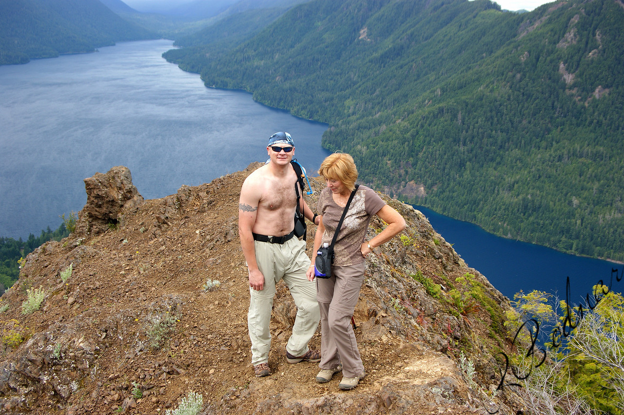 Photo By bob Bodnar...........................Greg & Sandy On Storm King Summit<br /> Looking Down on Lake Crescent<br />  State: Washington<br />  Location: Olympic National Park<br />  Length, One-Way: 1.7 miles<br />  Trail Type: Out and Back<br />  Minimum Elevation: 700 feet<br />  Maximum Elevation: 2700 feet<br />  Elevation Change: 2000 feet<br />  Trail Surface: Maintained<br />  Best Season: Summer<br />  Difficulty: Difficult<br />  Usage: Heavy