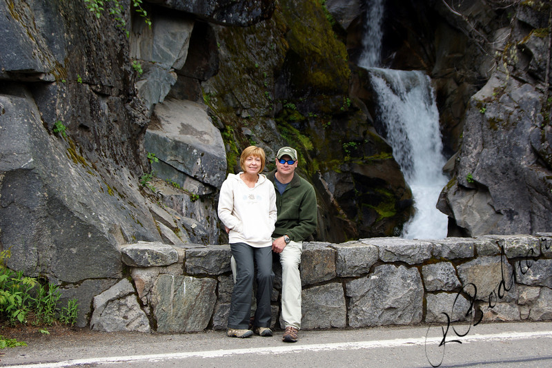 Photo By Bob Bodnar................Sandy & Greg at Christine Falls, Mt Rainier<br /> Christine Falls is the final waterfall along Van Trump Creek, falling 69 feet in drops of 32 and 37 feet respectively. The falls constitute one of the signiture views in Mount Rainier National Park, framed by the graceful Christine Falls Bridge. The falls have two tiers, one above and one directly underneath the bridge. Its unfortunately near impossible to get both the upper and lower tiers in the same photograph (it can be done with an ultra-wide lens, however). Geologically, Christine Falls has been one of the most unchanged waterfalls in the park, but on August 14th, 2001, a Glacial Debris Flow washed out of the Kautz Glacier and ran down Van Trump Creek. The flow left the entire creek canyon covered with mud, downed trees and rocks and as a result, Christine Falls has been altered. The lower tier remains the same, but a large chunk of rock fell out of the face of the upper tier, causing it to change form slightly. A more visible effect of the outburst flood, and the subsequent record setting floods in 2003 and especially in 2006 is that the creekbed has been scoured down to the bedrock, stripped free of all forms of vegetation.