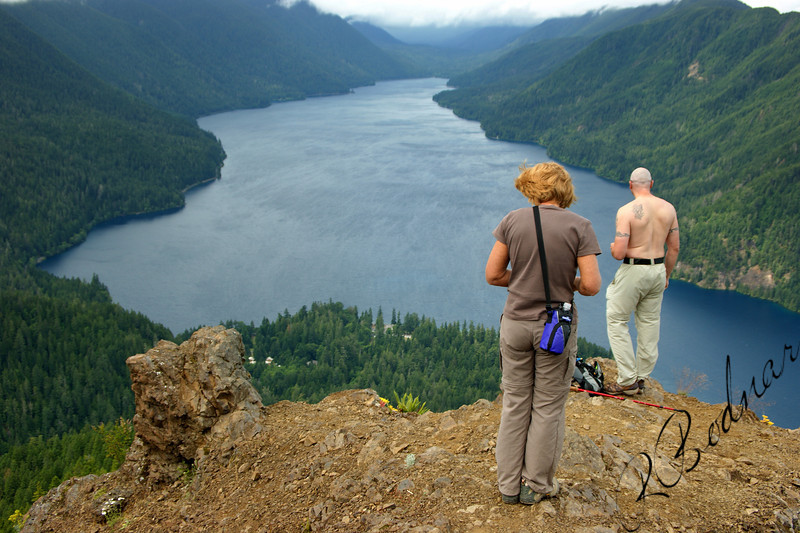 Photo By Bob Bodnar ........................Sandy & Greg on the summit of Storm King Mountain... Looking Down on Lake Crescent<br /> State: Washington<br />  Location: Olympic National Park<br />  Length, One-Way: 1.7 miles<br />  Trail Type: Out and Back<br />  Minimum Elevation: 700 feet<br />  Maximum Elevation: 2700 feet<br />  Elevation Change: 2000 feet<br />  Trail Surface: Maintained<br />  Best Season: Summer<br />  Difficulty: Difficult<br />  Usage: Heavy