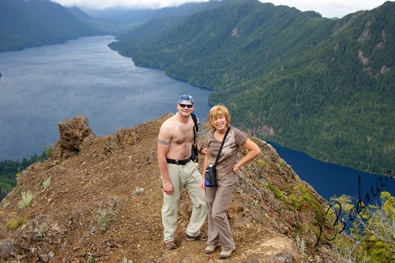 Photo By Bob Bodnar.......................Greg & Sandy On Storm King Summit<br /> Looking Down on Lake Crescent<br />  State: Washington<br />  Location: Olympic National Park<br />  Length, One-Way: 1.7 miles<br />  Trail Type: Out and Back<br />  Minimum Elevation: 700 feet<br />  Maximum Elevation: 2700 feet<br />  Elevation Change: 2000 feet<br />  Trail Surface: Maintained<br />  Best Season: Summer<br />  Difficulty: Difficult<br />  Usage: Heavy edit
